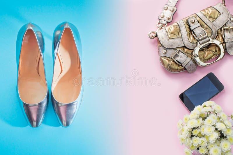 现代时装配件少妇穿上鞋子提包鞋子银色梯度蓝色花束花桃红色背景 库存照片