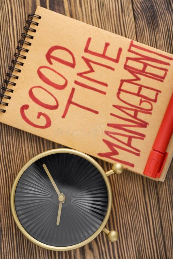 现代时钟和笔记本有词组美好时光时间安排的在木桌上 免版税库存照片