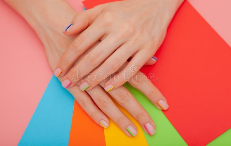现代时髦的修指甲彩虹或夏天心情,在一张桃红色桌上与颜色信封 免版税库存照片