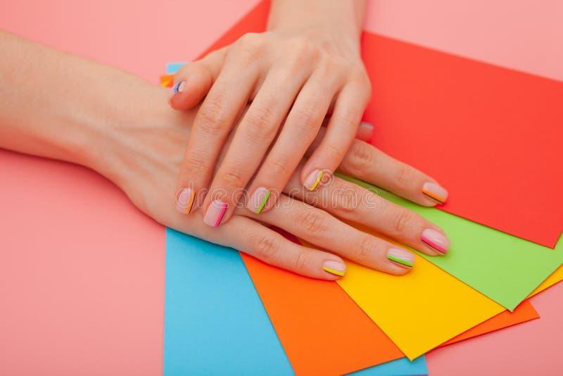 现代时髦的修指甲彩虹或夏天心情,在一张桃红色桌上与颜色信封 r 免版税库存图片