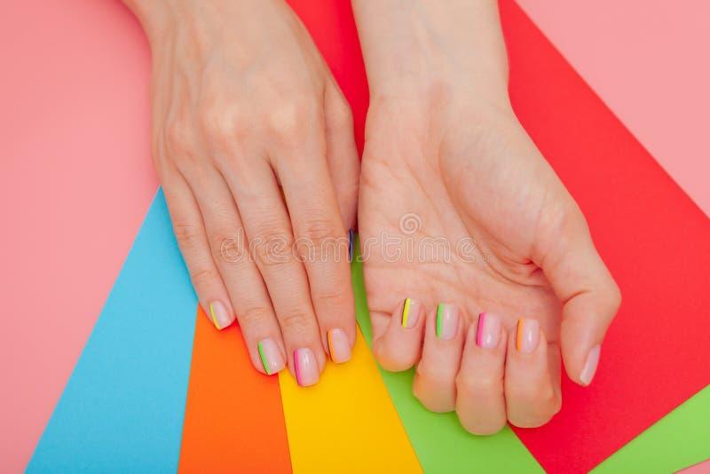 现代时髦的修指甲彩虹或夏天心情,在一张桃红色桌上有色的信封顶视图 库存图片