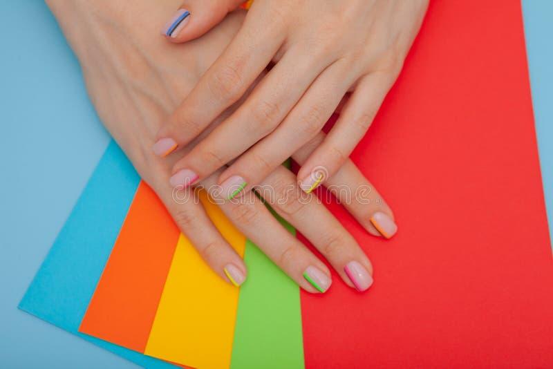 现代时髦的修指甲彩虹或夏天心情,在一张蓝色桌上与颜色信封 库存图片