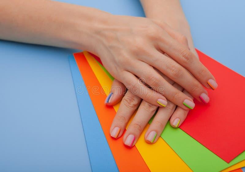 现代时髦的修指甲彩虹或夏天心情,在一张蓝色桌上有色的信封顶视图 库存图片