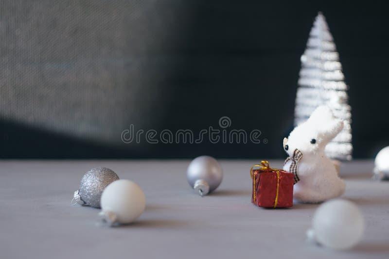 现代最小的圣诞节欢乐礼物冬天背景 接近的白色圣诞节快乐树,银色装饰品球,红色礼物盒 免版税库存图片