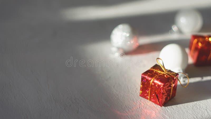 现代最小的圣诞节欢乐礼物冬天背景 红色礼物盒和白色xmas装饰品球的关闭在灰色水泥 库存照片