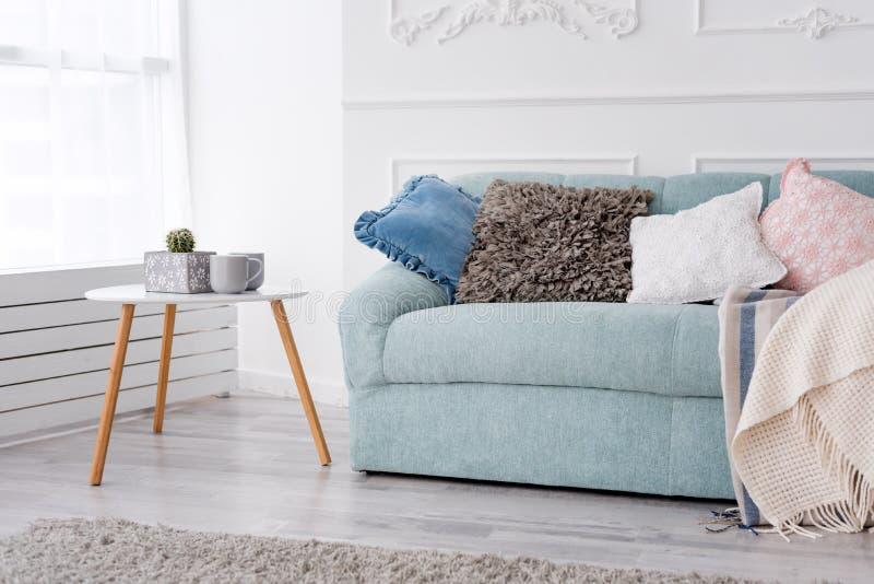 现代木咖啡桌和舒适沙发有枕头的 客厅内部和简单的现代家庭装饰概念 库存照片
