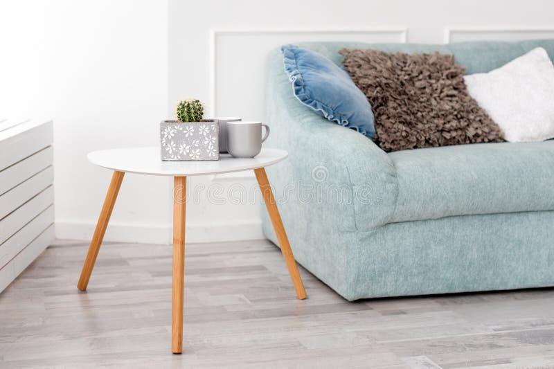 现代木咖啡桌和舒适沙发有枕头的 客厅内部和简单的现代家庭装饰概念 图库摄影