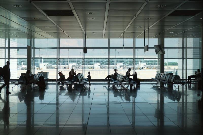 现代机场内部有乘客剪影的  免版税库存图片