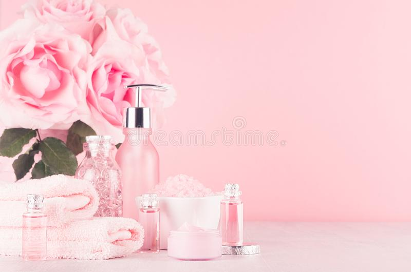 现代柔和的少女卫生间装饰-浴和温泉的,玫瑰,在软的白色木桌上的浴辅助部件花束化妆用品  免版税图库摄影