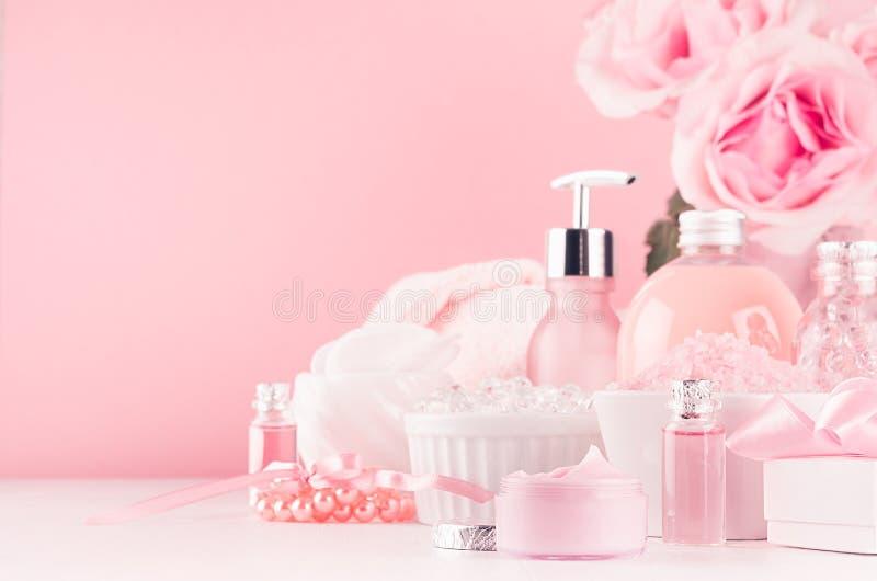 现代柔和的少女卫生间装饰-浴和温泉的,玫瑰,浴辅助部件,在软的白色木头的首饰花束化妆用品  免版税图库摄影