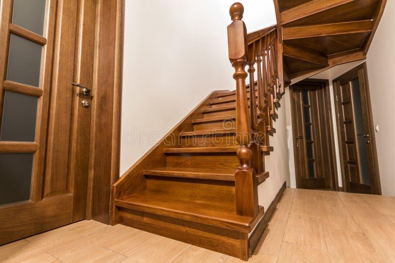 现代棕色橡木木台阶和门在新的被更新的房子里 免版税库存照片