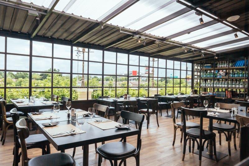 现代欧洲餐馆在半室外区域有从外部和透明屋顶的看法 库存照片