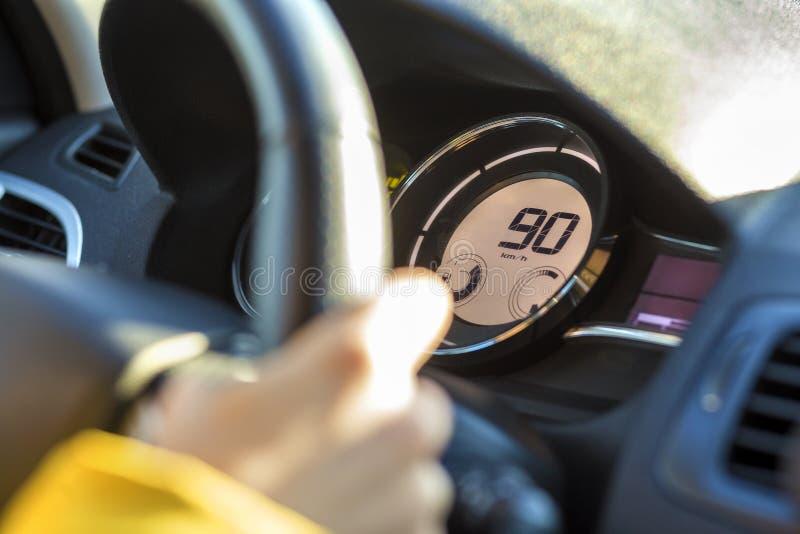 现代汽车内部用在方向盘的司机手和在车速表的九十km 安全驾驶的概念 图库摄影