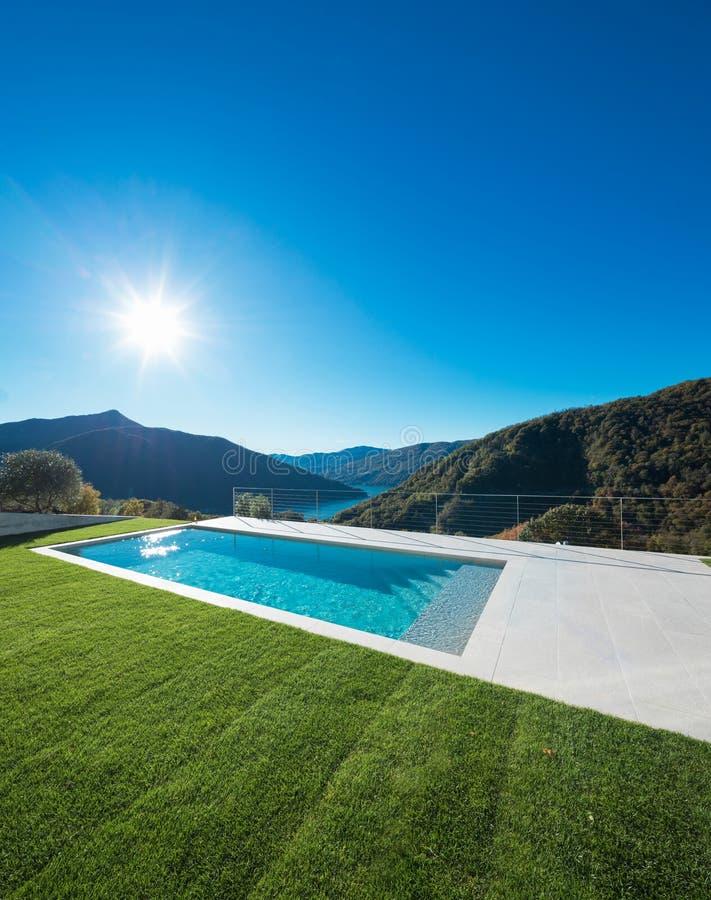 现代游泳池有湖和谷视图 免版税库存图片
