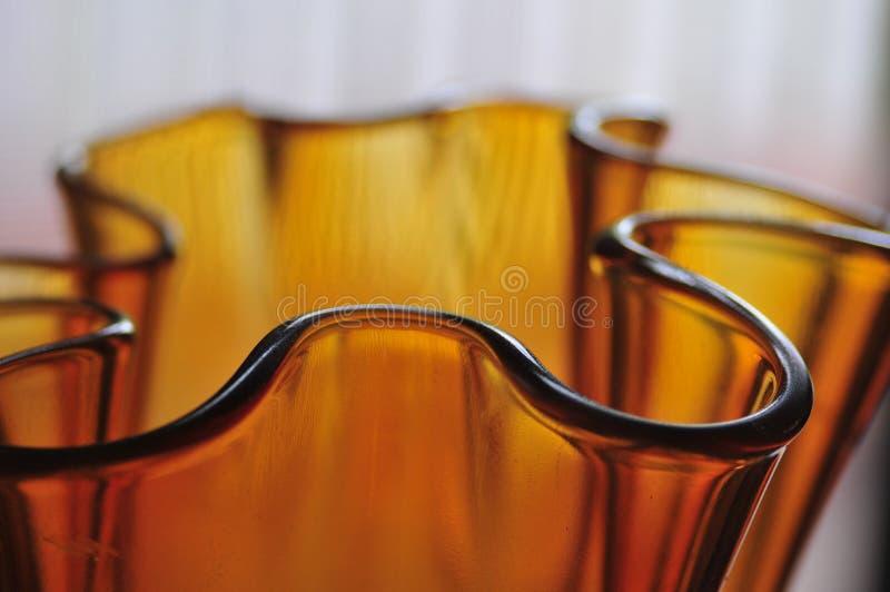现代琥珀色的玻璃艺术花瓶摘要心情弯曲系列Backgrou 库存照片