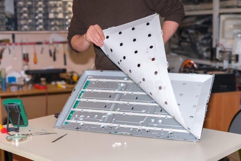 现代电视机修理  替换LED由后照与屏幕的拆卸 实际工作在服务中心 免版税图库摄影