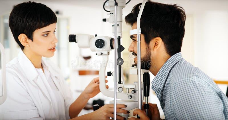 现代眼科学诊所的验光师审查的患者 免版税库存照片
