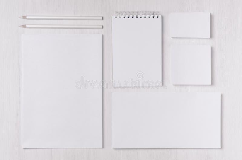 现代空白的白色企业文具设置了与卡片,标签,纸,在柔光白色木桌上的笔记薄 库存照片
