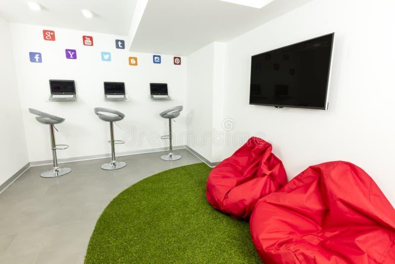 现代等待或者休息室室;膝上型计算机、电视和装豆子小布袋在背景中 免版税库存图片