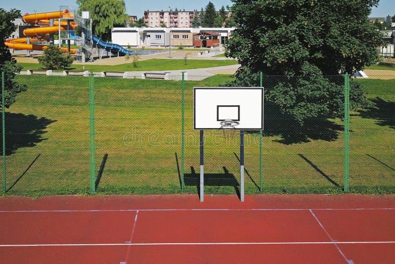 现代篮球场在小学庭院里  有浮出水面的人为的多功能儿童` s操场操刀 免版税库存图片