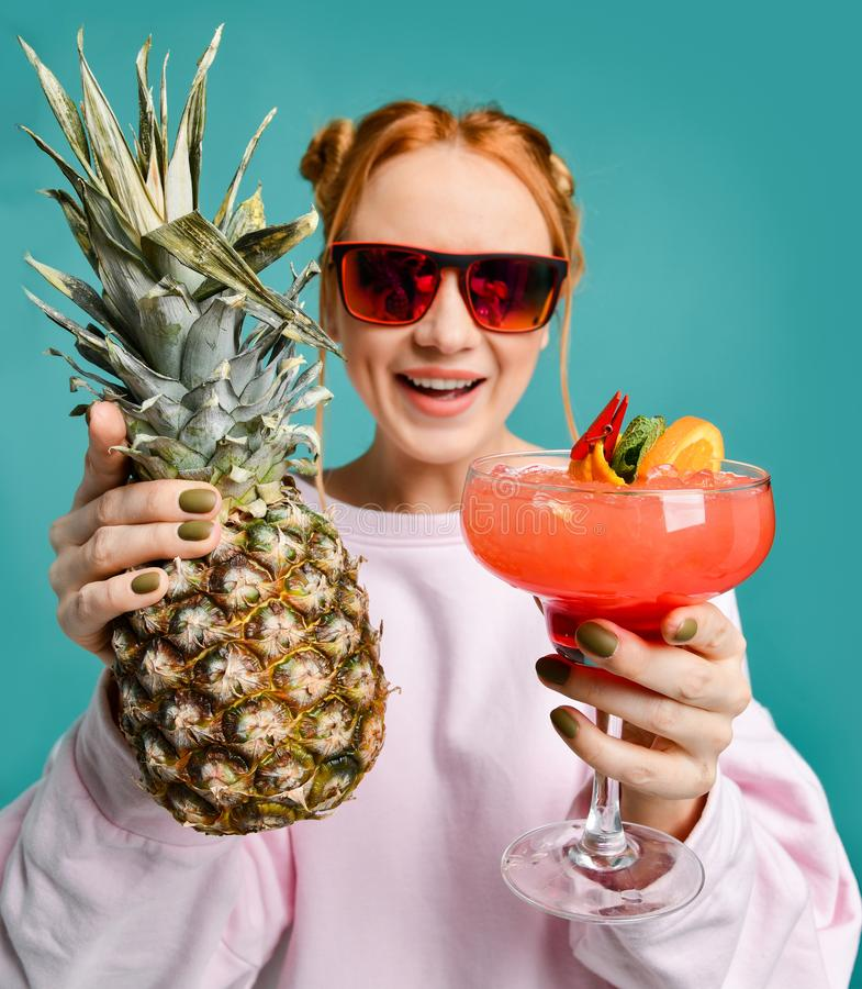 现代红色太阳镜的快乐的白肤金发的妇女递了我们展示草莓玛格丽塔酒鸡尾酒和一个大菠萝 库存照片