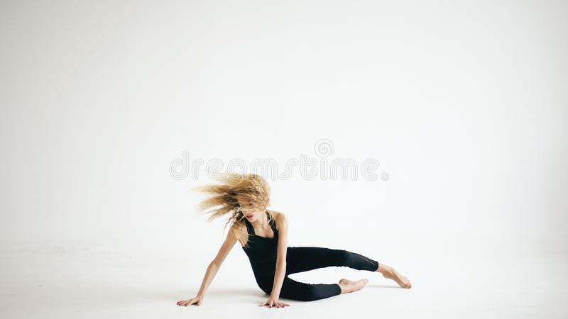 现代美丽的在白色背景的十几岁的女孩舞蹈家跳舞的当代户内 库存照片