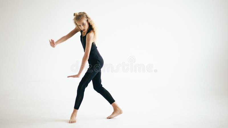 现代美丽的在白色背景的十几岁的女孩舞蹈家跳舞的当代户内 库存图片