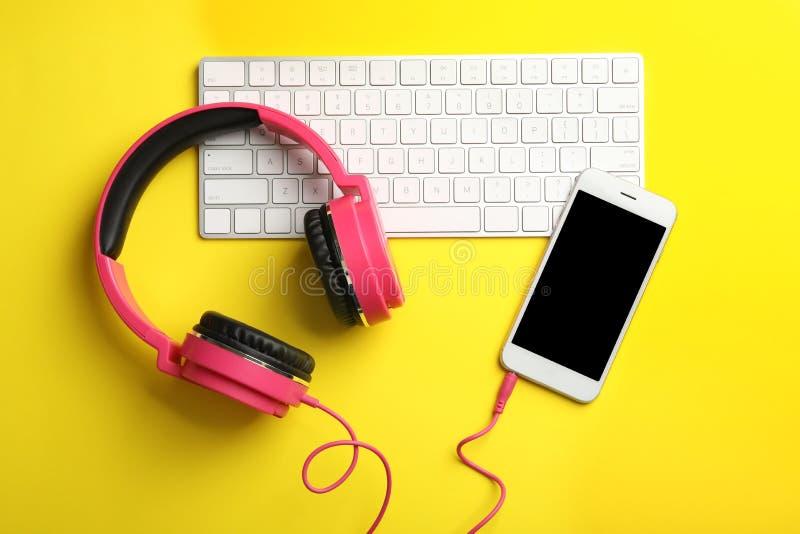 现代耳机、电话和键盘在颜色背景,平的位置 免版税库存照片