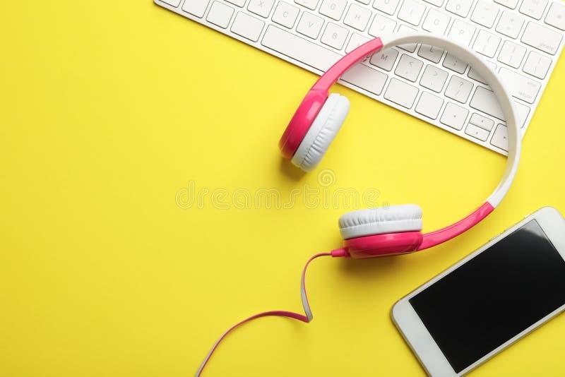 现代耳机、键盘和电话在颜色背景,平的位置 库存照片