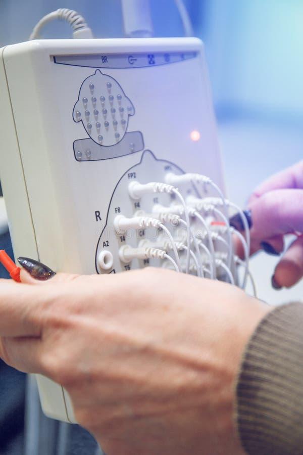 现代脑X光检查法和医生手有导线的在诊所 EEG或脑波记录仪研究 库存照片