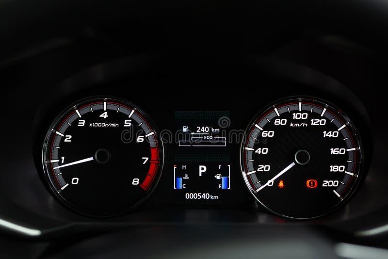 现代英里汽车仪表板仪表盘的关闭内部与警告灯、游乐器具和手煞车光 免版税库存图片