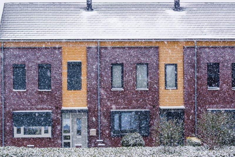 现代荷兰露台的家在一寒冷冬天天,多雪的天气期间在荷兰的一个小村庄 免版税库存照片