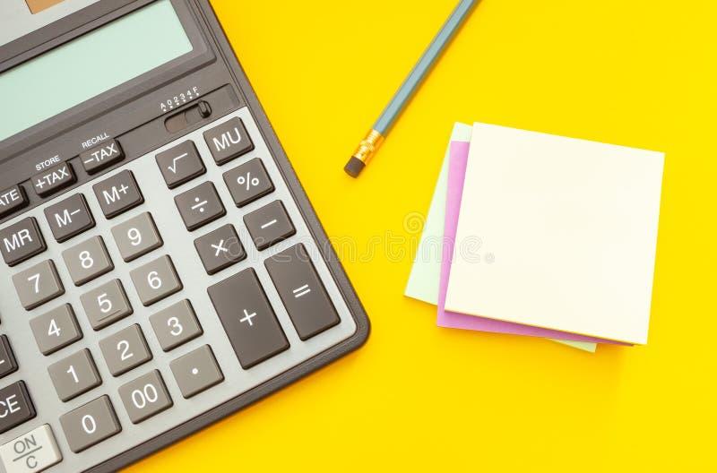 现代计算器和铅笔有贴纸的笔记的关于黄色背景,顶视图 库存图片