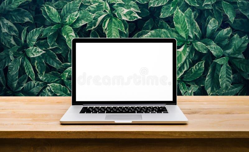 现代计算机,有黑屏的膝上型计算机在与绿色叶子的桌上 图库摄影
