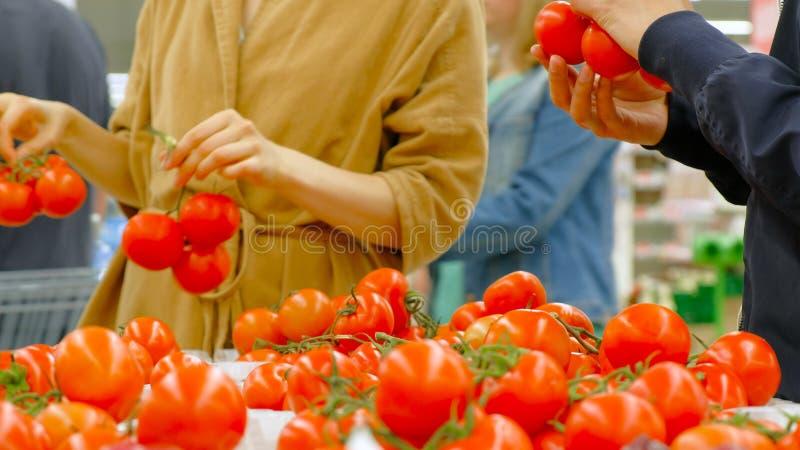 现代超级市场访客选择红色新鲜的蕃茄 免版税库存图片