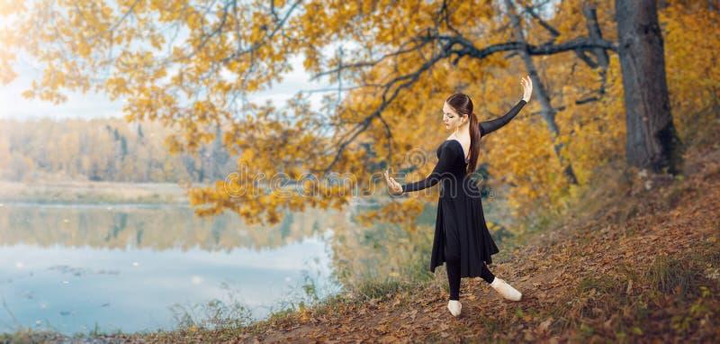 现代跳芭蕾舞者在秋天公园 免版税库存图片
