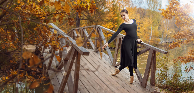 现代跳芭蕾舞者在秋天公园 免版税库存照片