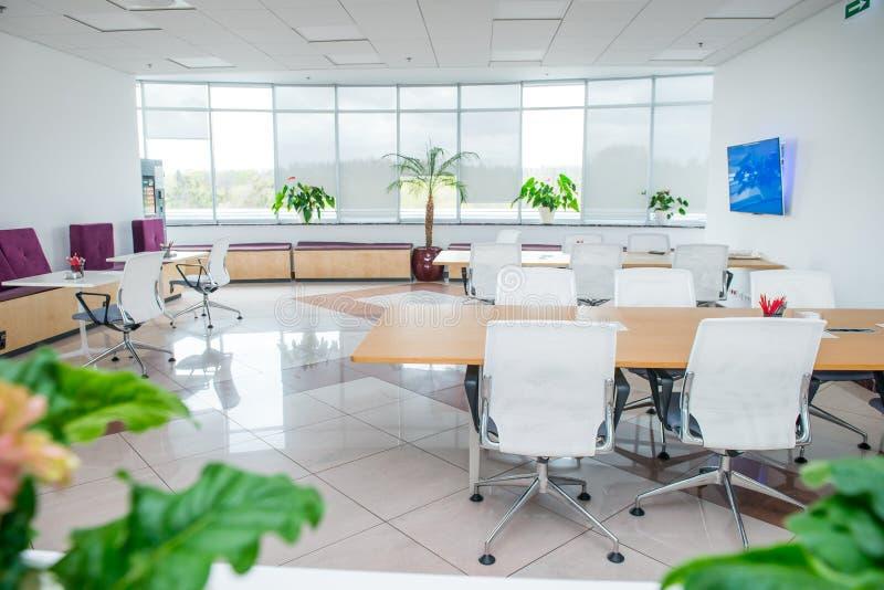 现代轻的空的露天场所办公室内部有大窗口、桌书桌、椅子和绿色植物的 Coworking工作场所conce 库存照片