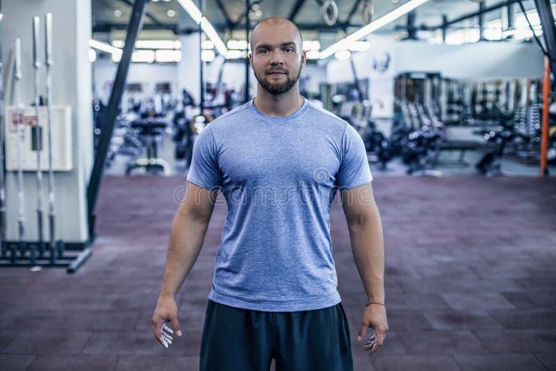 现代运动员 看照相机的体育衣物的英俊的年轻人,当站立在健身房时 库存照片