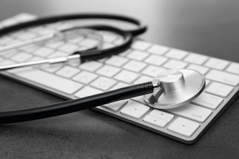 现代键盘和听诊器在桌上 库存图片