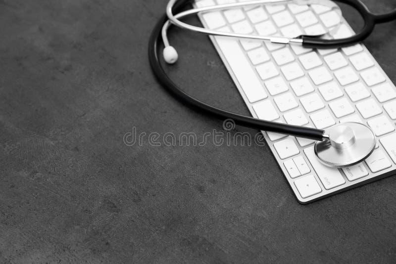 现代键盘和听诊器在桌,空间上文本的 免版税库存图片