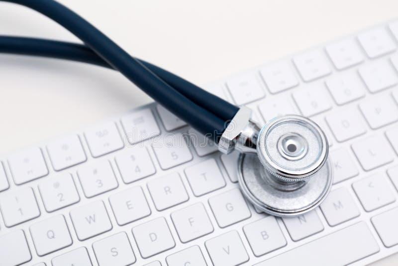 现代键盘和听诊器在轻的背景 库存图片