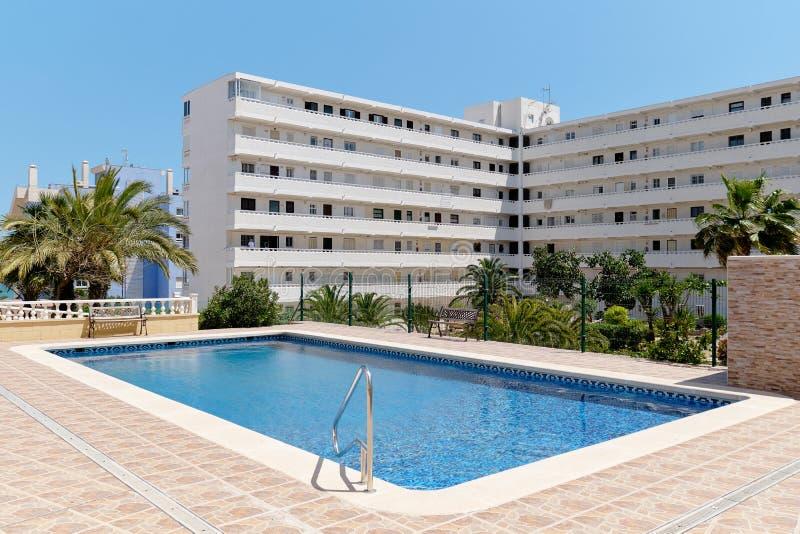 现代高层多层的住宅房子外部,与公开游泳场的闭合的区域 免版税库存图片