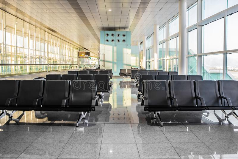 现代黑位子几行在机场的空的晴朗的等待的大厅里 寂寞,等待的概念,旅行, 库存照片