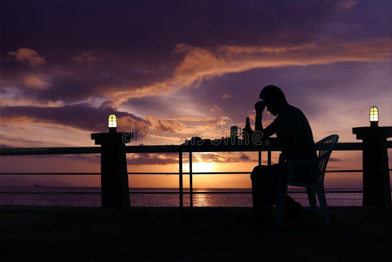 现出轮廓哀伤的人饮用的啤酒在与红色天空sunse的海滩 库存照片