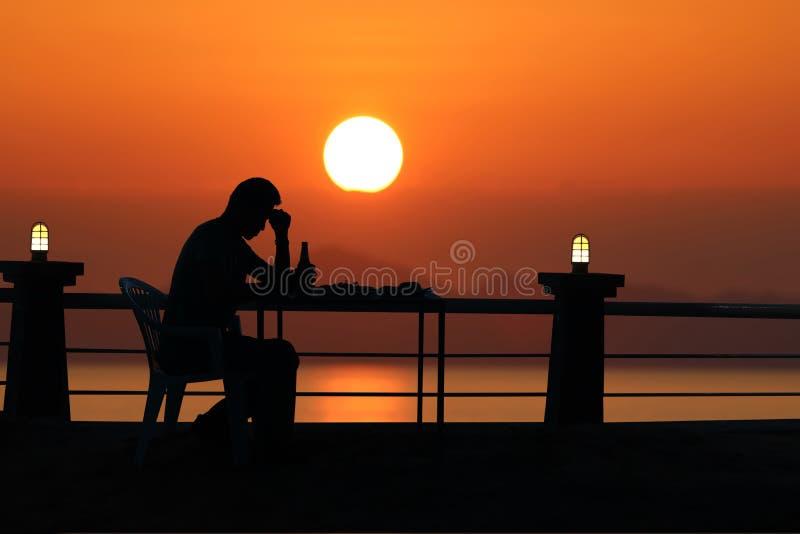 现出轮廓哀伤的人饮用的啤酒在与红色天空sunse的海滩 免版税库存图片