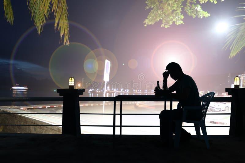 现出轮廓哀伤的人饮用的啤酒在酒吧,夜光 免版税库存图片
