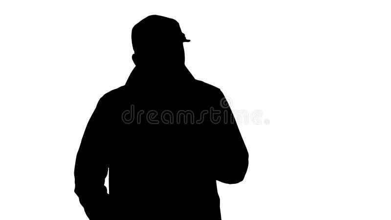现出轮廓在军用防水短大衣穿戴的一个正面有胡子的男性走和谈话 皇族释放例证