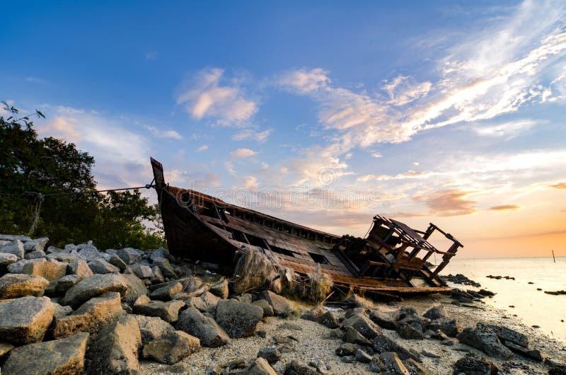 现出轮廓在岩石海岸线遭受海难的摒弃的图象 黑暗的云彩和软绵绵地在水 免版税图库摄影