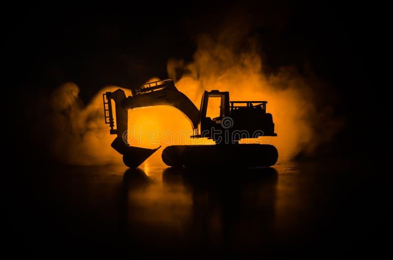 现出轮廓在黑暗的有雾的红色橙色天空背景的被跟踪的挖掘机与玩具汽车 空的空间 库存照片